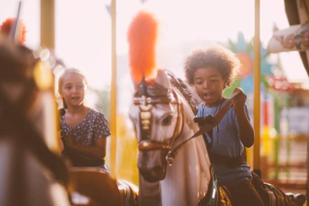 multi-ethnischen kinder haben spaß im freizeitpark karussell fahren - karussell stock-fotos und bilder
