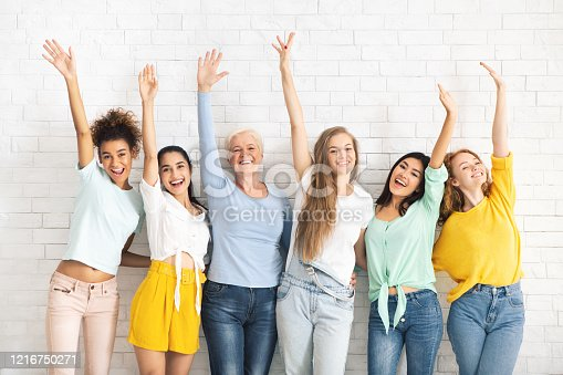866758230 istock photo Multiethnic Ladies Waving Hands Posing Against White Brick Wall Backgound 1216750271