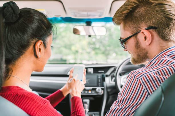 multiethnic lover couple, white man and black asian girl using navigator system app on smart phone in car. modern gadget lifestyle, family travel activity, or online taxi call request service concept. - rideshare stock photos and pictures