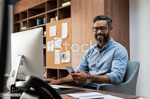 Smiling business man wearing eyeglasses working on desktop computer while using phone in office. Middle eastern businessman using smartphone while sitting at desk in office designer. Man working in modern business environment.