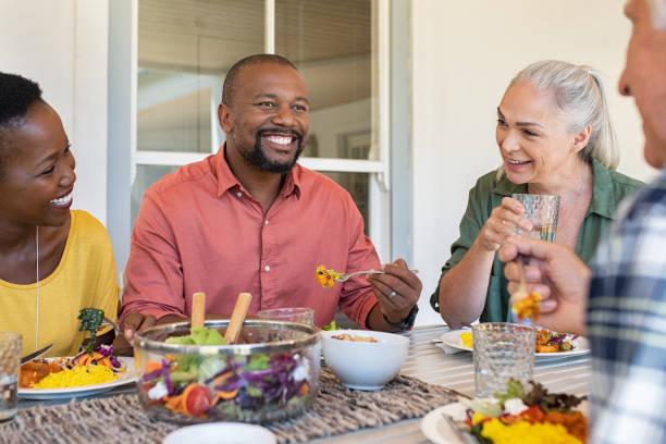 los hombres y mujeres maduros multiétnicos que comen el almuerzo - couple lunch outdoors fotografías e imágenes de stock