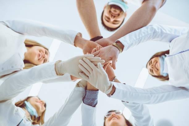 multiethnic medical team stacking hands in circle for success - procedura medica evento foto e immagini stock