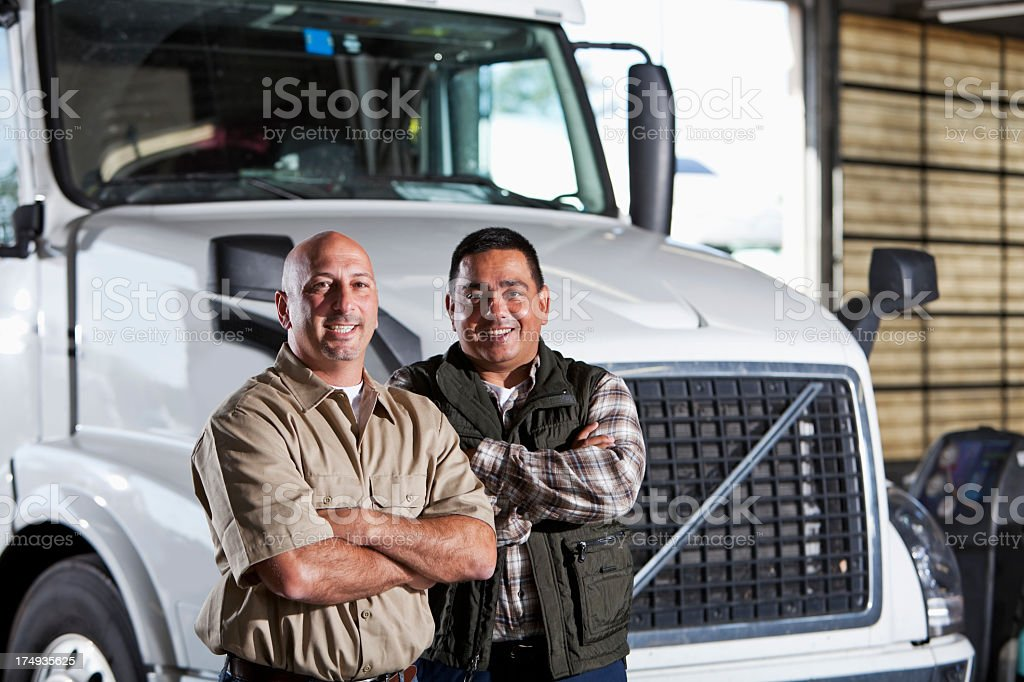 Multi-ethnic men standing next to semi-truck royalty-free stock photo