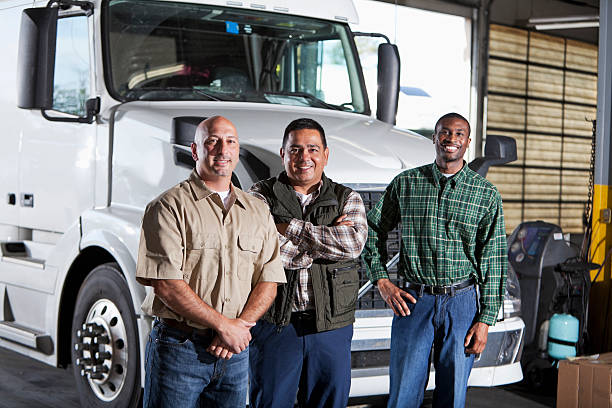 multiétnico hombre de pie junto a semi-truck - conductor de autobús fotografías e imágenes de stock