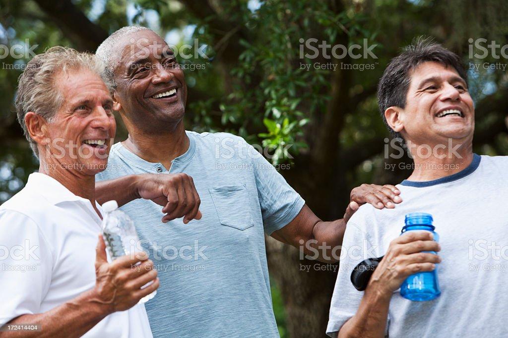 Multi-ethnic men taking break from exercising stock photo
