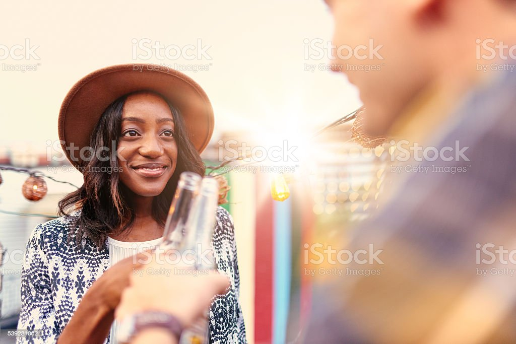 Multi-ethnic millenial couple flirting while having a drink on stock photo