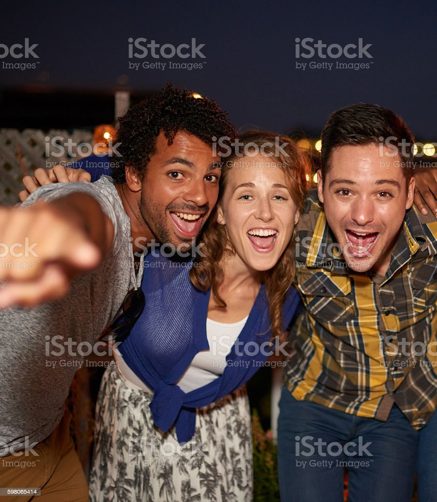 Multi-ethnic millenial friends taking a flash selfie with mobile stock photo
