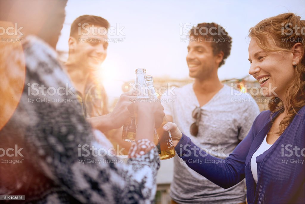 Multi-ethnic millenial group of friends partying and enjoying a stock photo