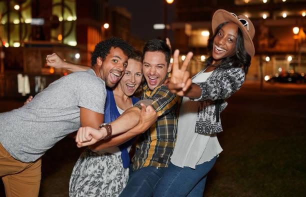 multi-ethnique millenial groupe d'amis prenant un selfie photo - vie nocturne photos et images de collection