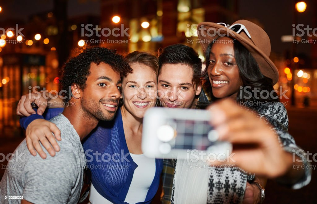 Multi-ethnic millenial group of friends taking a selfie photo with mobile phone on rooftop terrasse using flash at night time stock photo