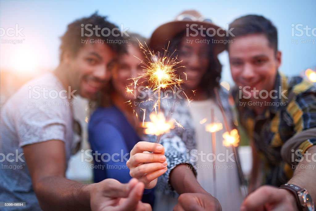 Multi-ethnic millenial group of friendsfolding sparklers on rooftop terrasse stock photo