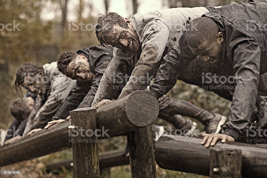 Multiethnic mud run team of men climbing along obstacle course stock photo