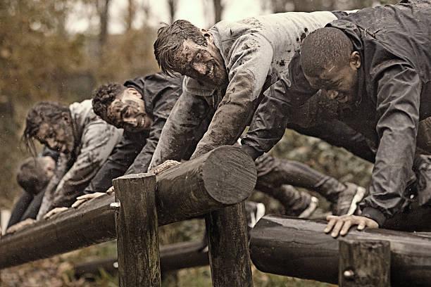 multiethnic mud run team of men climbing along obstacle course - militärisches training stock-fotos und bilder