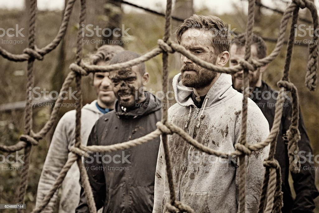 Multiethnic mud run team of men preparing for obstacle course stock photo