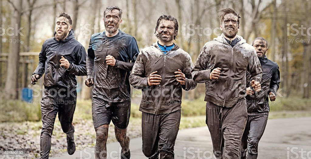 Multiethnic mud run team of men running during obstacle course stock photo