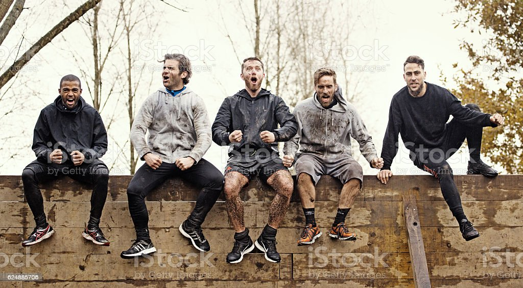 Multiethnic mud run team of men sitting on obstacle course stock photo