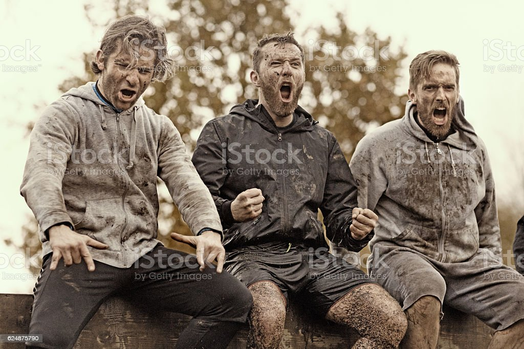 Multiethnic mud run team of men sitting shouting obstacle course stock photo