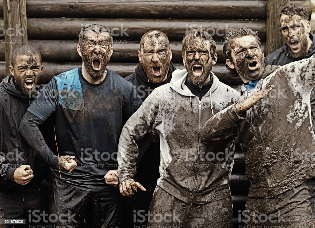 Multiethnic mud run team of men yelling during obstacle course - Royalty-free Active Lifestyle Stock Photo