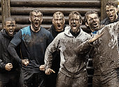 Multiethnic mud run team of men yelling during obstacle course