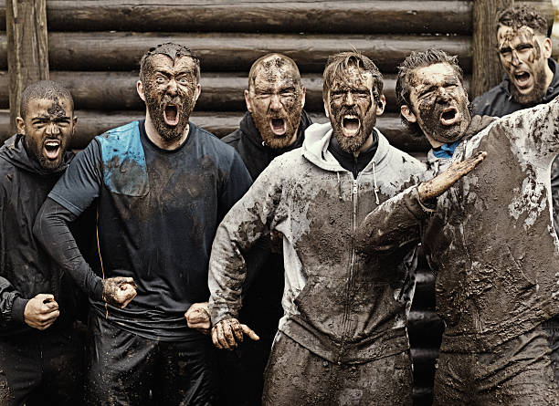 Multiethnic mud run team of men yelling during obstacle course stock photo