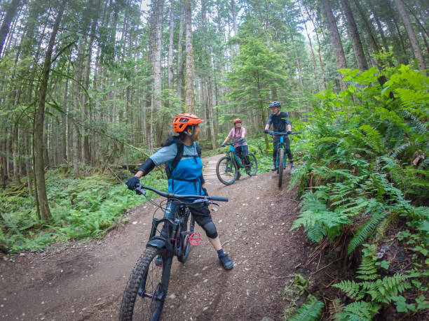 Multi-Ethnic, Multi-Generation Family and Friends Mountain Biking on Forest Trail stock photo