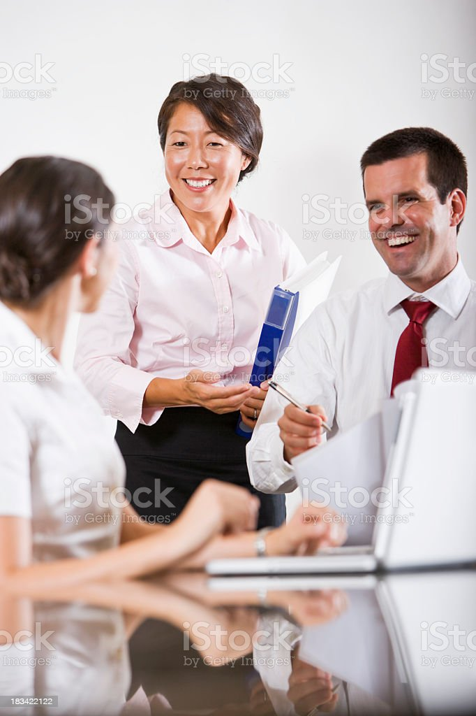 Multi-ethnic office workers in boardroom talking and using lapto royalty-free stock photo