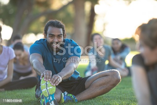 A group of multi-ethnic young adults sit n the grass outside stretching their legs.  They are smiling and wearing comfortable active wear