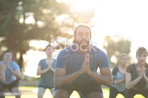 A group of multi-ethnic young adults are outside in the grass doing yoga fitness.  They are squatting with their hands in the prayer pose, smiling and wearing comfortable active wear.
