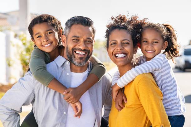 многоэтнические родители давая детям piggyback ездить - family стоковые фото и изображения
