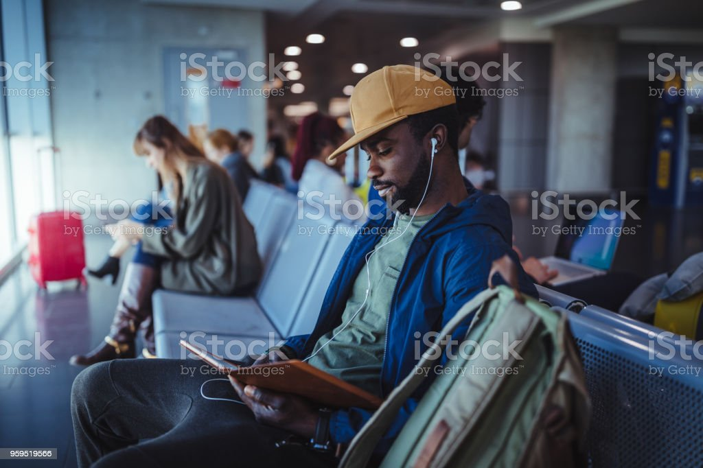 Multi-ethnic passengers sitting on bench and waiting at airport stock photo