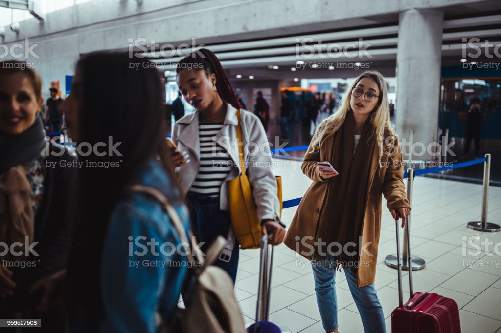 Multi-ethnic passengers standing in queue for check-in at airport stock photo