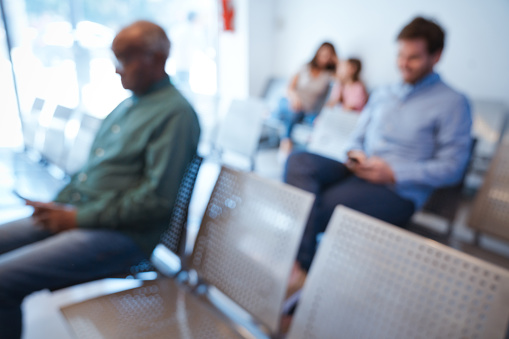 istock Multi-ethnic patients sitting in waiting room 1136841423