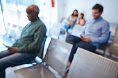 Defocused image of patients waiting at hospital. Multi-ethnic people are at waiting room. They are sitting on seat.
