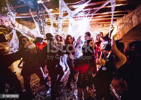 istock Multi-ethnic people in Halloween costumes having fun at dungeon nightclub 915628830