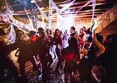 Multi-ethnic people in Halloween costumes having fun at dungeon nightclub