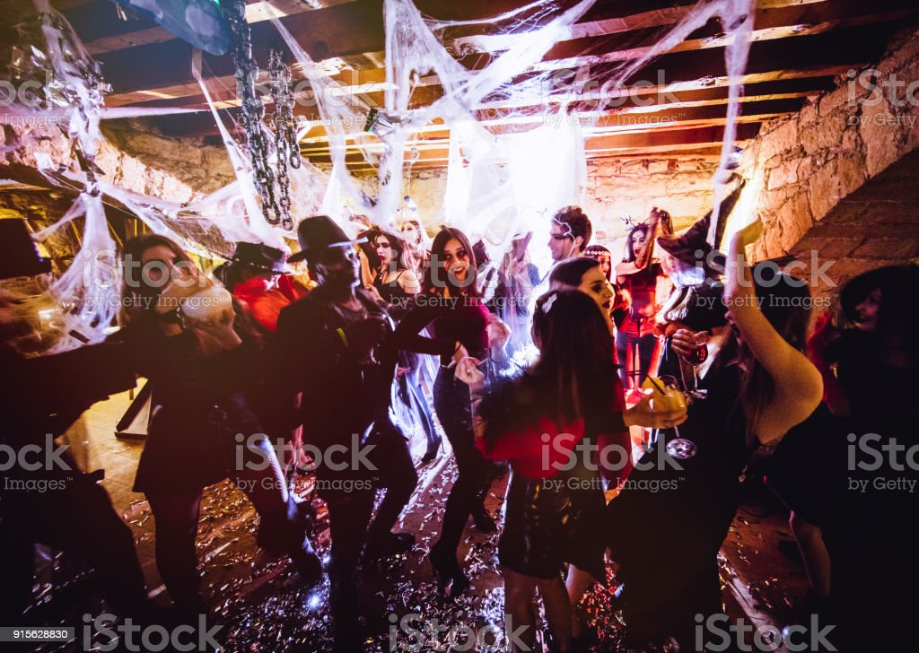 Multi-ethnic people in Halloween costumes having fun at dungeon nightclub stock photo