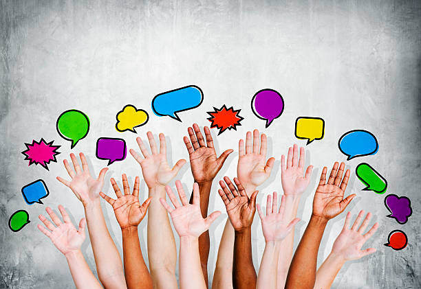 Multiethnic People's Hands Raised with Speech Bubble Multiethnic people's hands raised with speech bubble by concrete wall. debate stock pictures, royalty-free photos & images