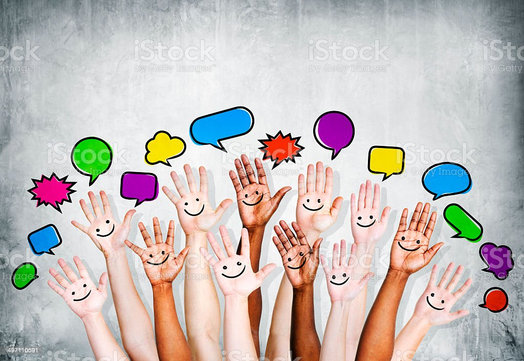 Multiethnic People's Hands Raised with Speech Bubble stock photo