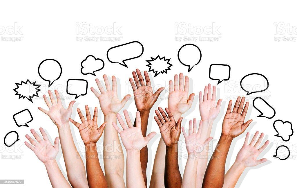 Multiethnic People's Hands Raised with Speech Bubble stock photo