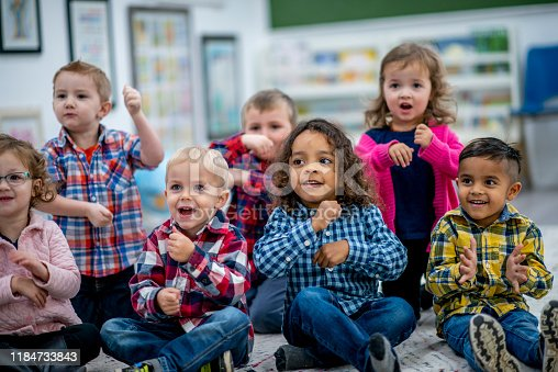 A group of multi-ethnic preschool students sit on a classroom rug.  They are singing, doing actions, clapping and having fun during a sing-along time.  Each is wearing casual clothing in bright colors.