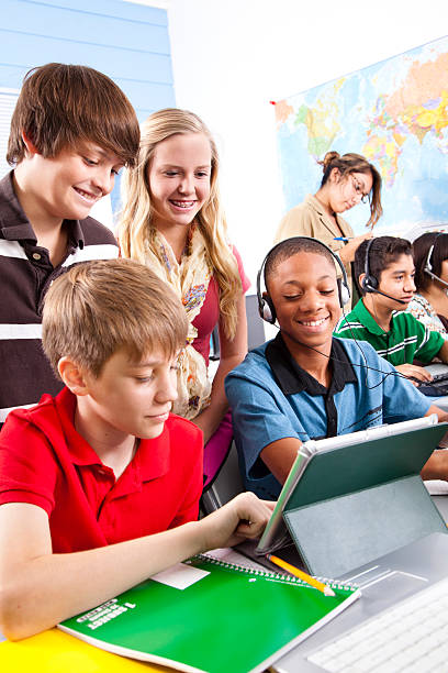 multi-ethnic preteen students. computer lab school classroom. digital tablet. teacher. - middle school teacher stock pictures, royalty-free photos & images