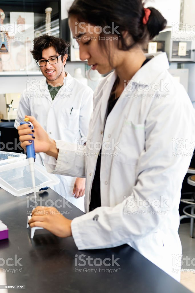 Multi-ethnic professor and student in college science laboratory. stock photo