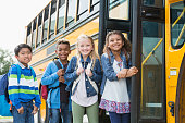 A group of four multi-ethnic school children standing outside the open door of a school bus, smiling at the camera. The mixed race black and Caucasian girl on the right and Asian boy on the left are 8 years old and their friends are 9. They are elementary school students.