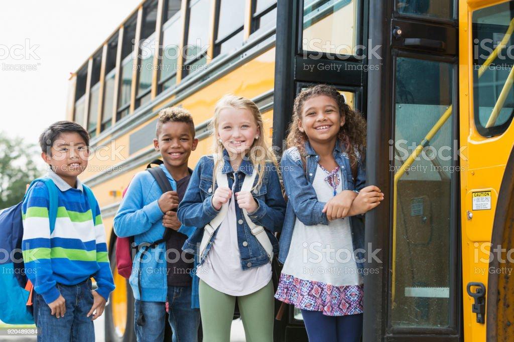 Escolares multiétnicos pie exterior bus - foto de stock