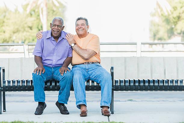 Multi-ethnic senior men hanging out on park bench - Photo