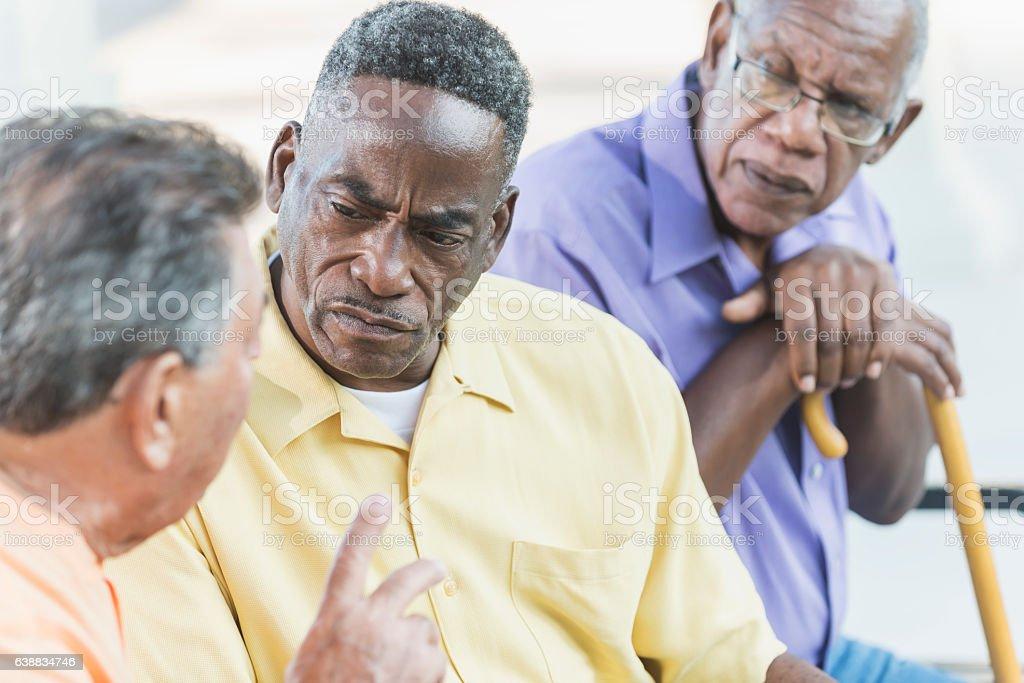 Multi-ethnic senior men on park bench, talking stock photo