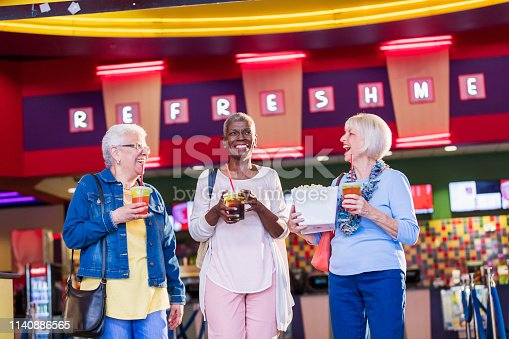 A group of three multi-ethnic seniors having fun together at the movies. They are carrying popcorn and drinks from the concession stand. The woman on the right is in her 70s, her friends, in their 60s, are African-American and Hispanic.