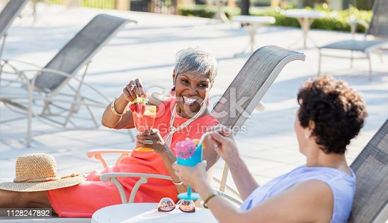 Two multi-ethnic senior women relaxing together on lounge chairs by the pool, having tropical drinks, talking and laughing. The focus is on the African-American woman who is in her 70s.