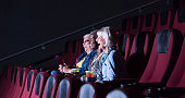 A group of three multi-ethnic seniors sitting together in a movie theater, watching a comedy film, laughing.