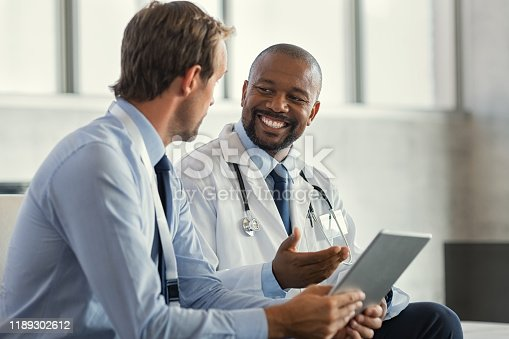 Two mature smiling doctors having discussion about patient diagnosis, holding digital tablet. Successful african surgeon discussing case after positive result. Representative pharmaceutical discussing with african happy doctor about new medicine.